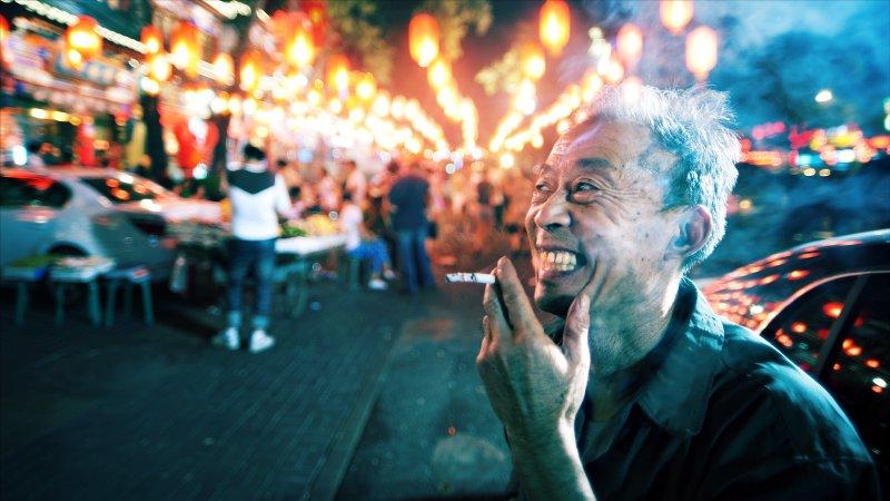 Fotografia przedstawiająca obywatela ChRL zpapierosem