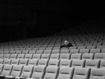 Okładka podcastu random:self - fotografia widza wpustej sali kinowej