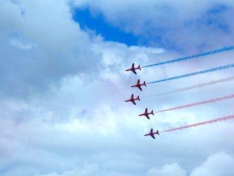 Fotografia pokazu lotniczego: samoloty na tle chmur rozpylające kolorowe wstęgi dymu